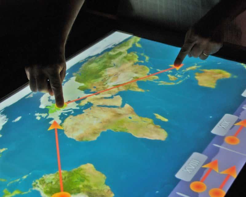 Mains manipulant une carte sur un écran tactile