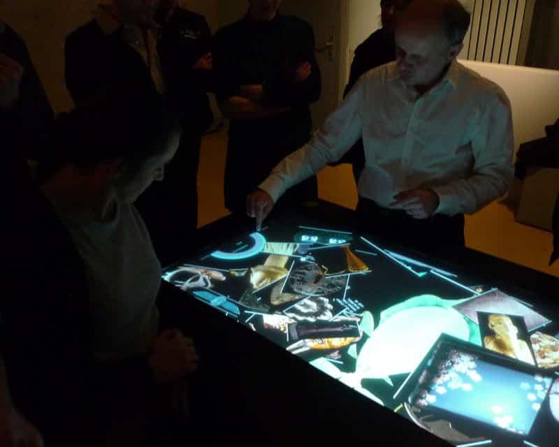 Homme présentant l'outil Museotouch autour d'une table tactile